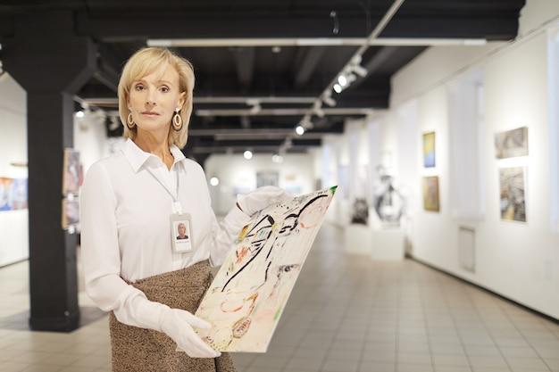 Женский арт эксперт позирует в галерее