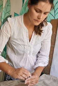女性職人の陶芸家が粘土層にレタリングの印象を与える