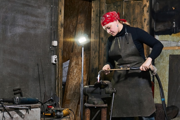 Female artisan handles a metal artwork clamped in a vice with an welding machine in a workshop