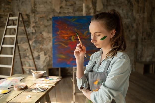 女性アーティストがブラシで顔に緑色の絵の具を塗る
