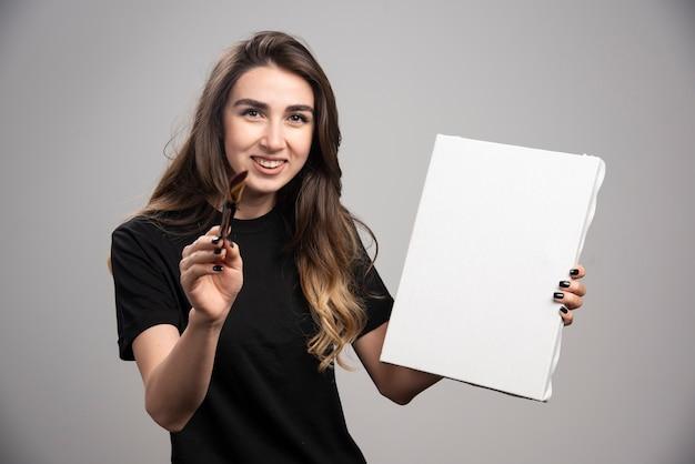 Artista femminile in camicia nera che tiene strumenti artistici.