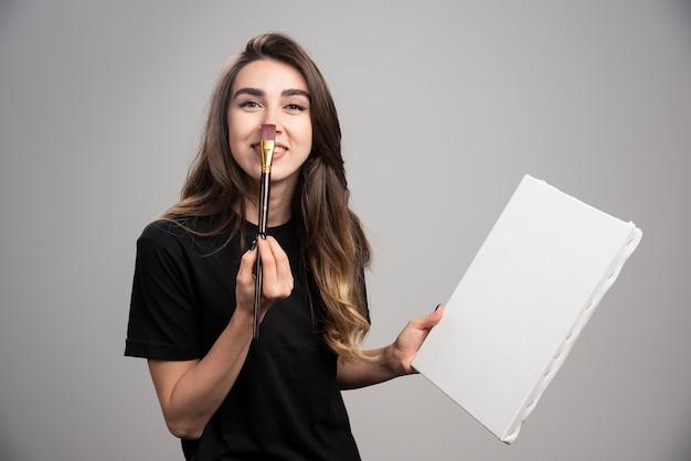 Artista femminile in camicia nera che tocca il suo naso con la spazzola.