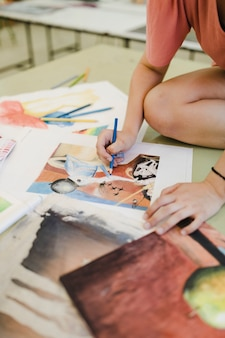 Female artist coloring with blue pencil on canvas paper