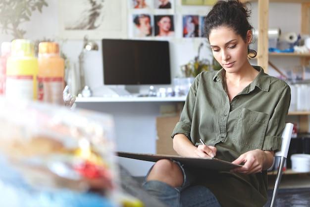 女性アーティストはカジュアルな服装で、何かを描きながらワークショップに座ってスケッチに取り組みました。クリエイティブな女性が絵画に関わっています。人、趣味、創造的なプロセスの概念