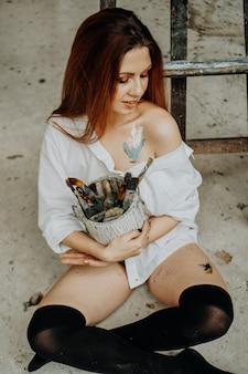 Female artist hand holding paintbrush at art workshop