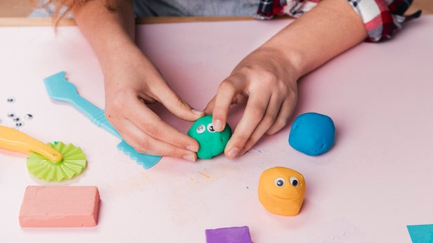 Female artist hand making cartoon faces using soft clay