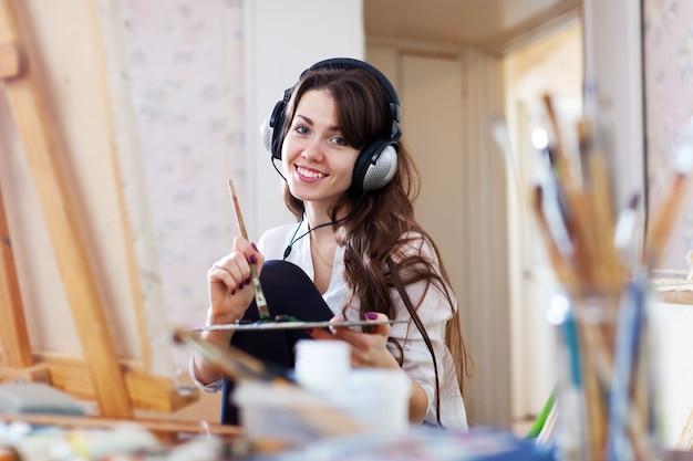 Female artist in headphones paints picture