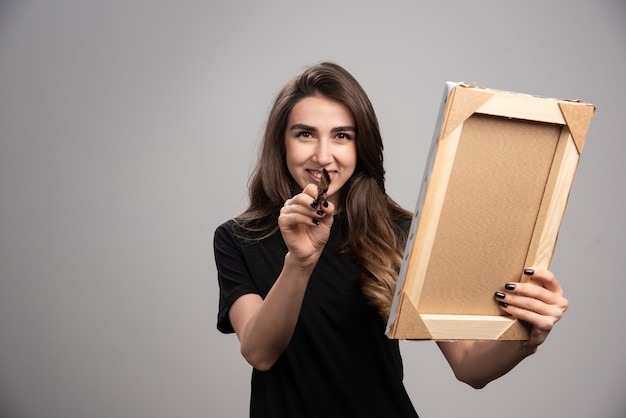 Female artist holding brush and picture frame.