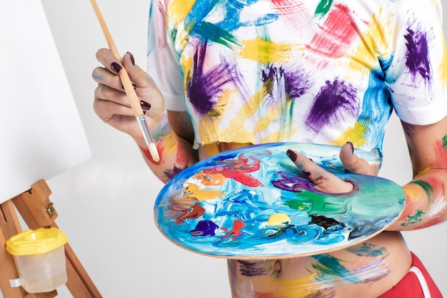 絵の具でパレットを保持している女性アーティスト