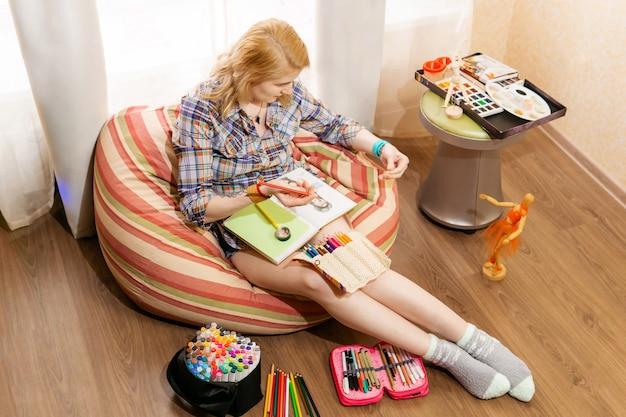 女性アーティストのイラストレーターが小さなマネキンを見ながら、自宅のノートにスケッチを描く