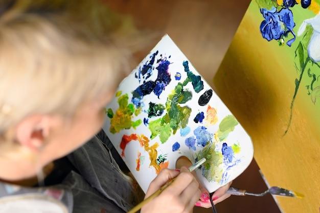 Художница смешивает краски на палитре художник в студии, создатель создает произведение искусства