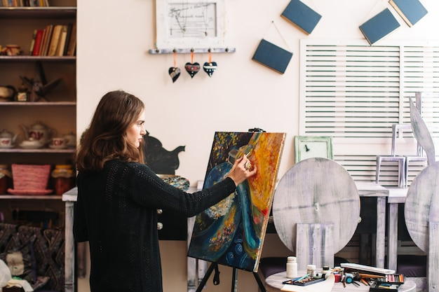 スタジオで抽象的なアートワークを描く女性アーティスト