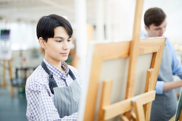 Female artist painting on easel