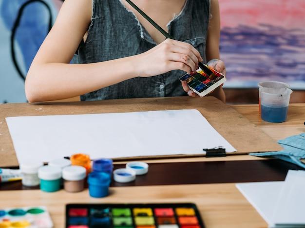 Художница рисует в творческой рабочей области