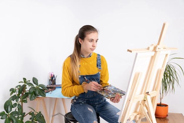 Художница рисует в мастерской на белом фоне