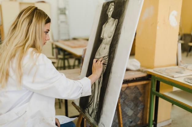 ワークショップのイーゼルに描かれた女性アーティスト