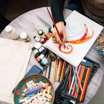 アートスタジオで紙に絵を描く女性アーティスト