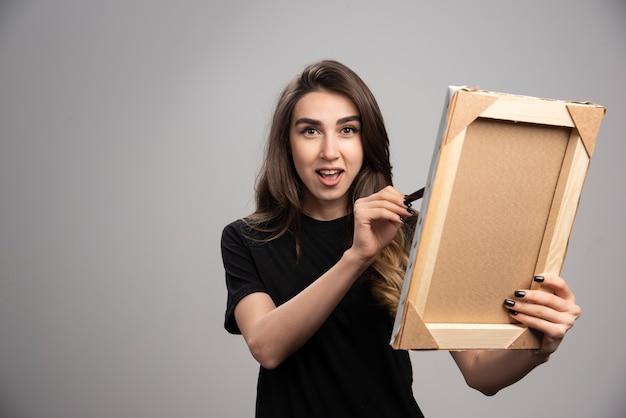 Женский художник рисует в рамке.