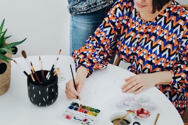 딸이 보고 있는 동안 그림을 그리는 여성 예술가