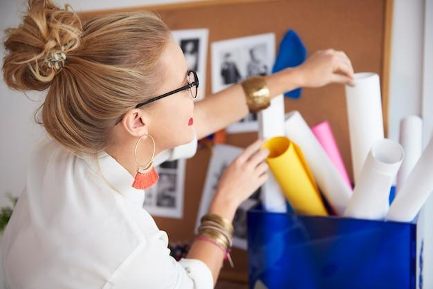 紙のロールに手を伸ばす女性アーティスト