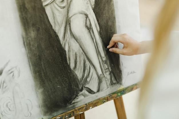 キャンバスでイーゼルにスケッチする女性アーティストの手