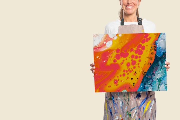 Female artist showing a canvas with fluid artwork