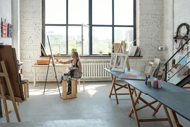 キャンバスの前に座って、自分の広々としたスタジオで絵を描く女性アーティスト