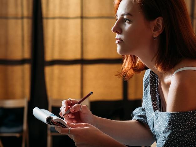 女性アーティストのスケッチ。描くことを学ぶ。パッドで鉛筆スケッチをしている赤毛の女性。
