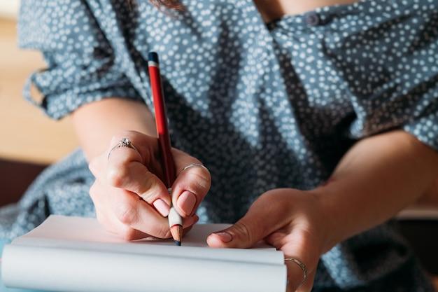 女性アーティストのスケッチ。描くことを学ぶ。鉛筆スケッチのクローズアップをしている女性。