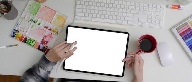 空白の画面のタブレットで作業する女性アーティスト、ペイントツール、オフィスの机の上のコーヒーを飲む