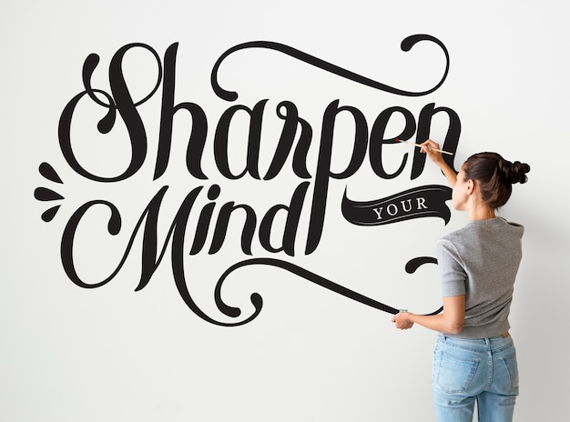 Female artist writing sharpen your mind quote on the wall