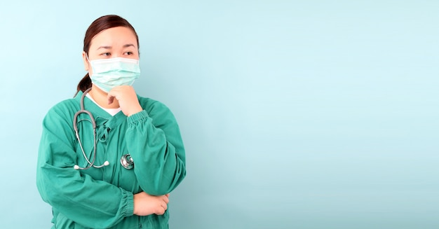 여성 아시아 외과 의사, 외과 의사 복사 공간을 가진 스튜디오에서 보호 마스크 감염 증 및 코로나 바이러스 또는 covid-19 입고 청진기를 보여주는 불안 느낌.