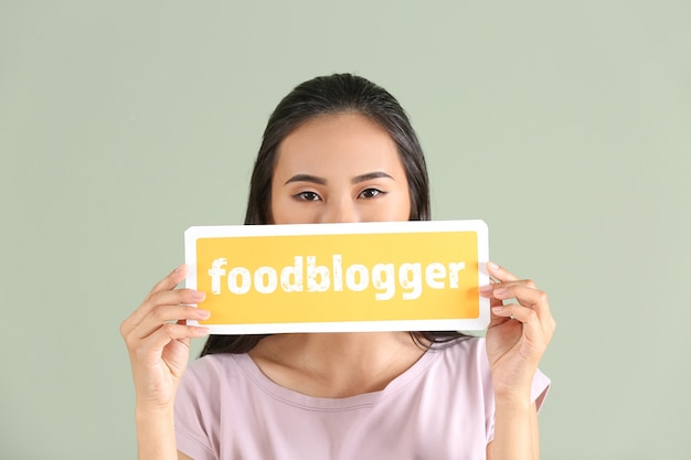 Female asian blogger holding paper with text foodblogger on color background