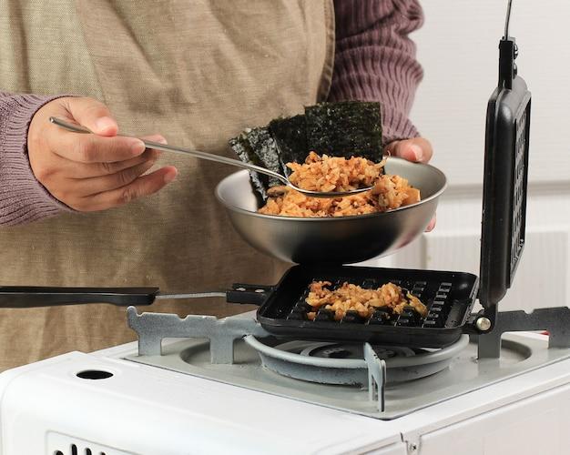 Азиатский шеф-повар готовит вафли с жареным рисом кимчи (kimchi bokkeumbap) или вафлями наси горенг, модный вирусный рис, прессованный с помощью вафельницы, популярный в южной корее