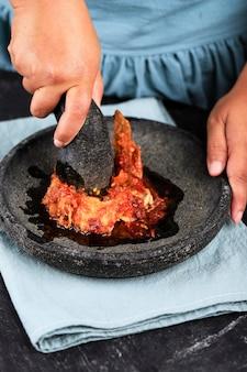 인도네시아의 인기 있는 길거리 음식인 아얌 게프렉(ayam geprek)을 만들거나 요리하는 과정에서 인도네시아 모르타르와 페슬을 곁들인 매운 칠리 페이스트를 곁들인 여성 아시아 손으로 으깬 프라이드 치킨.