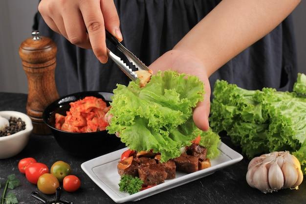 여성 아시아 손 양상추에 마늘을 넣어, 쌈 만드는 과정, 김치와 양상추 랩, 한우 바베큐, 쌀, 마늘, 고추장
