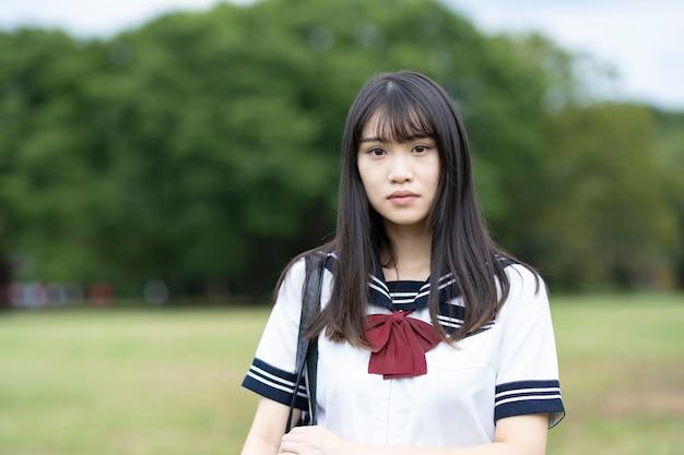 Азиатская старшеклассница со спокойным взглядом на открытом воздухе