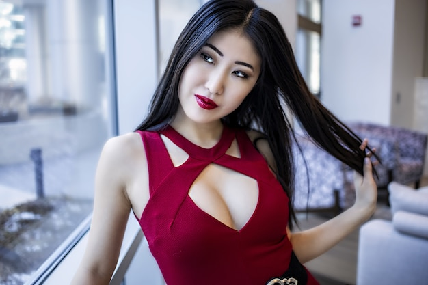 女性のアジア人モデルの顔。ファッショナブルな赤い口紅とドレスを着て