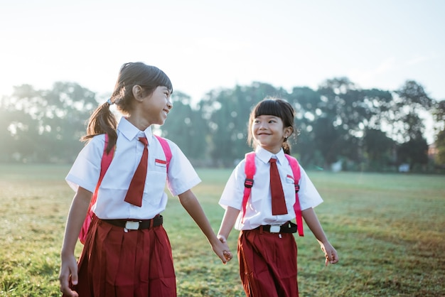 Female asian primary first grader student walk together