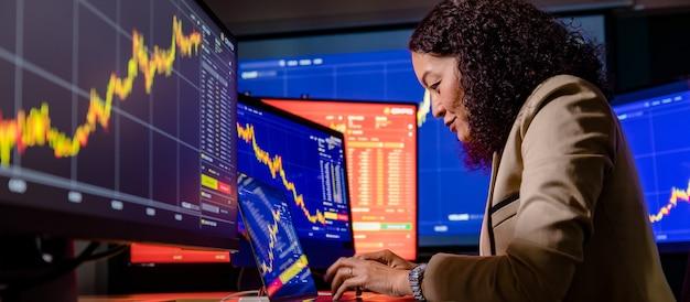 女性のアジアの成功したプロのブローカートレーダー投資家がラップトップコンピューターの学習チャートに入力