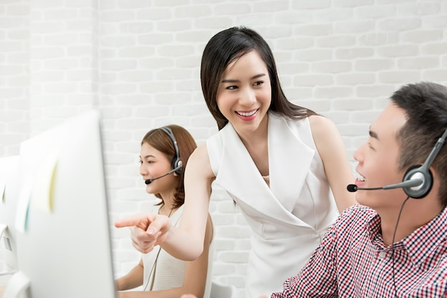 Female asian supervisor discussing work with customer service team in call center