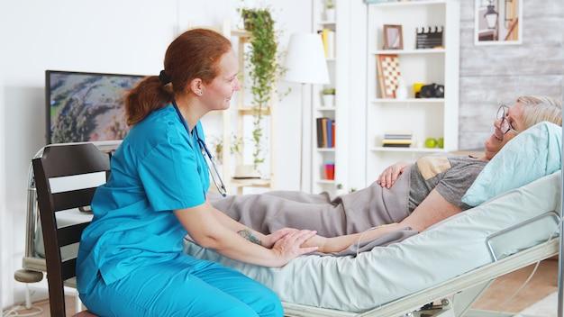 요양원의 여성 조수는 병원 침대에 누워 있는 노부인의 손을 잡고 그녀와 이야기하고 있다