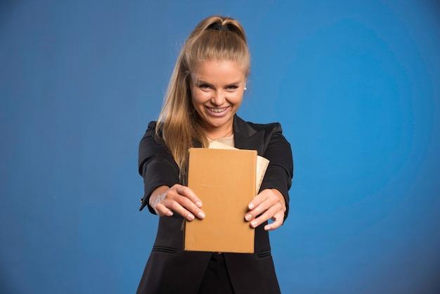 Женский помощник держит блокнот в кожаном переплете и демонстрирует задания.