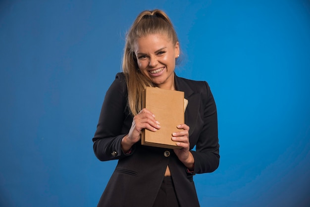 Female assistant holding a leather cover notebook and demonstrating tasks.