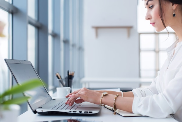 女性アシスタントが働いて、タイピングして、ポータブルコンピューターを使って、集中して、モニターを見ています。ビジネスの電子メールを読んでいるサラリーマン。