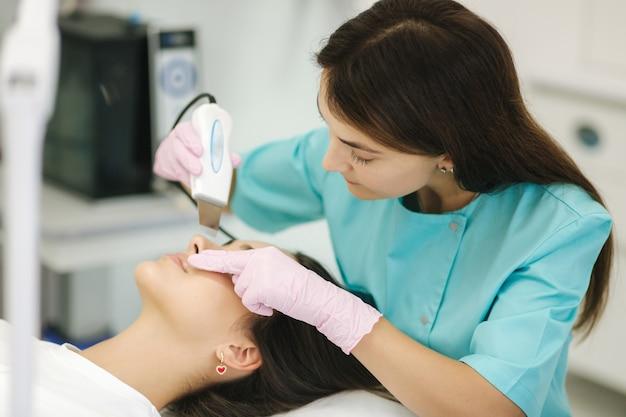 Женщина в косметической спа-клинике занимается аппаратной косметологией лица. женщина делает процедуры красоты