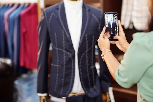 マネキンにほぼ準備ができているオーダーメイドのジャケットを撮影している女性のアトリエマネージャー