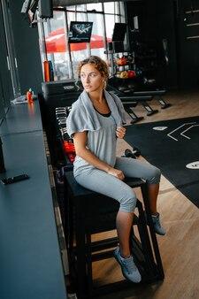 신체 운동 후 여성 운동 선수는 f의 체육관 개념의 흐린 배경에 땀 수건으로 달려 있습니다.