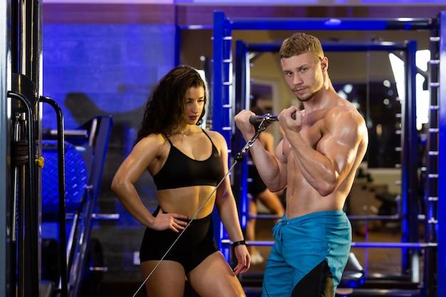 Спортсменка и мужчина-спортсмен тренируются вместе в тренажерном зале