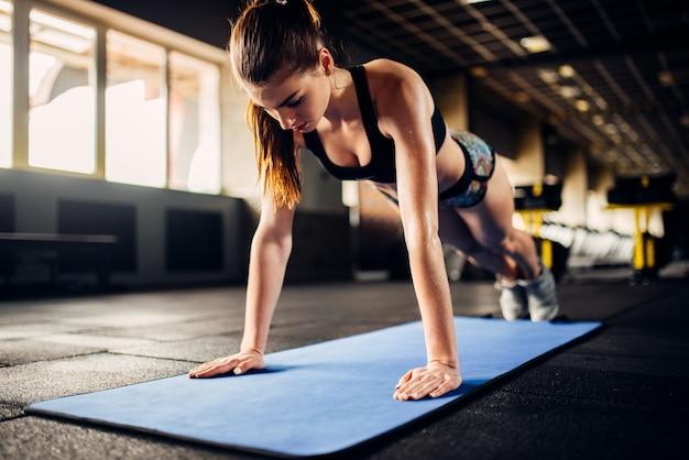 Спортсменка делает упражнения отжимания на тренировке в спортивном зале. молодая женщина в фитнес-клубе